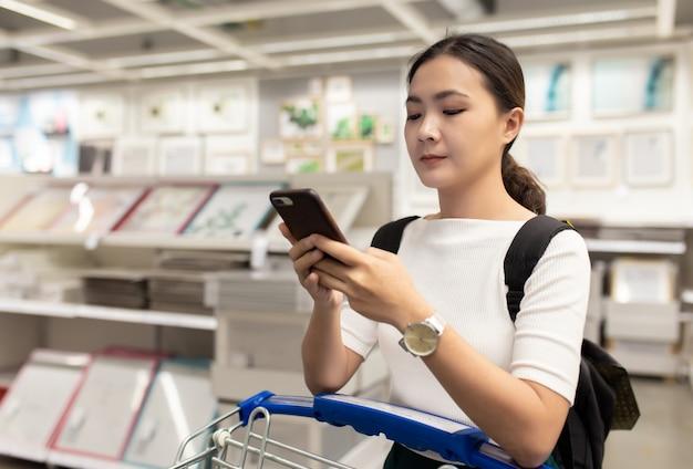Mulher com carrinho de compras na loja e usar telefone inteligente para verificar preço