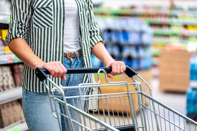 Mulher com carrinho de compras no supermercado. compra de comida no supermercado. compras de supermercado