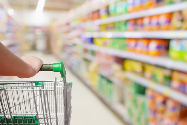 Mulher com carrinho de compras verde procura comida no supermercado