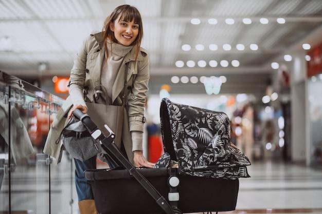 Mulher, com, carruagem bebê, em, shopping, centro comercial