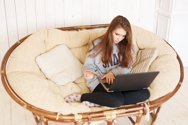 Mulher, com, cartão crédito, usando computador portátil, para, shopping online