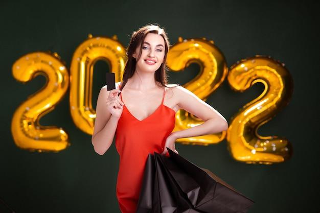 Mulher com cartão de crédito e compras ano novo, compras, vendas de balões negros de sexta-feira