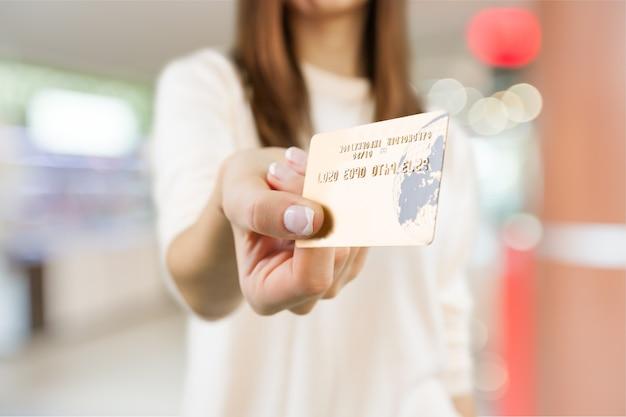 Mulher com cartão de crédito, segurando com a mão.