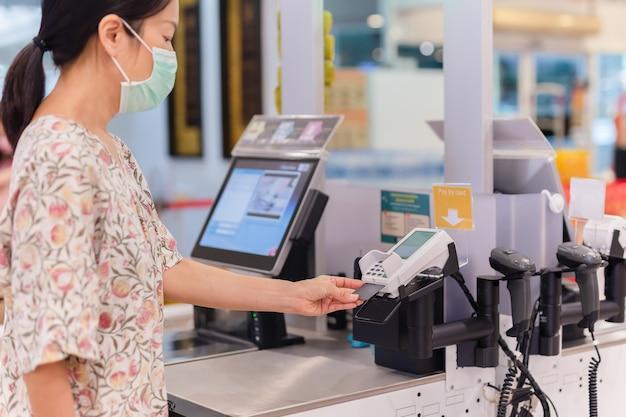 Mulher com cartão do banco pagando comida no supermercado selfcheckout