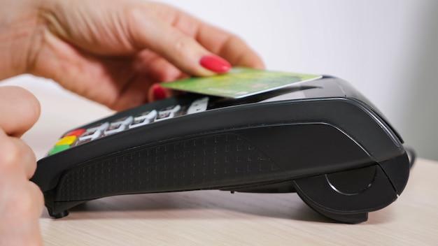 Mulher com cartão está usando o terminal para pagamento, transação sem dinheiro, terminal emite um cheque, close-up das mãos, vista lateral.