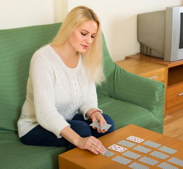 Mulher com cartões no interior da casa