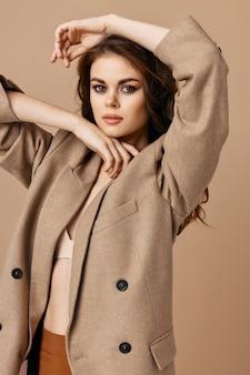 Mulher com casaco de aparência atraente estúdio de cosméticos de moda