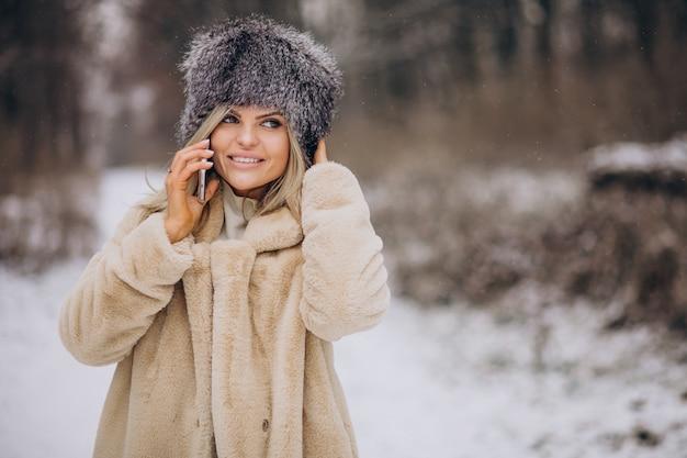 Mulher com casaco de inverno caminhando em um parque cheio de neve falando ao telefone