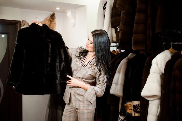 Mulher com casaco de pele. menina com um casaco de pele na loja de peles