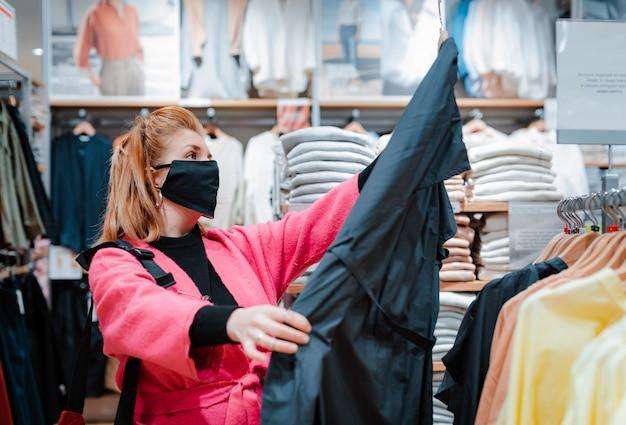 Mulher com casaco de shopping rosa brilhante telefone com máscara protetora preta no rosto de vírus infectados ar.