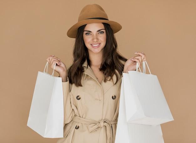 Mulher com casaco e chapéu em fundo marrom
