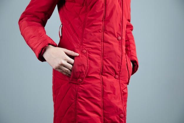Mulher com casaco no bolso em estúdio