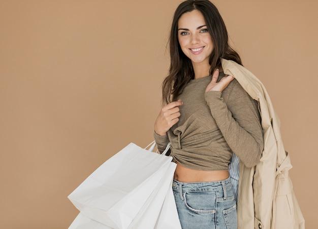 Mulher com casaco no ombro e sacolas de compras