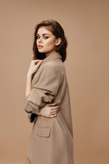 Mulher com casaco se abraça com as mãos no modelo de maquiagem penteado com fundo bege