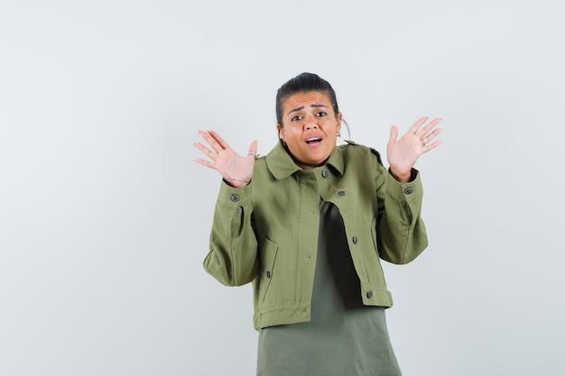 Mulher com casaco, t-shirt com as palmas das mãos em gesto de rendição e parecendo assustada