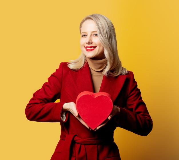 Mulher com casaco vermelho e caixa de presente na parede amarela