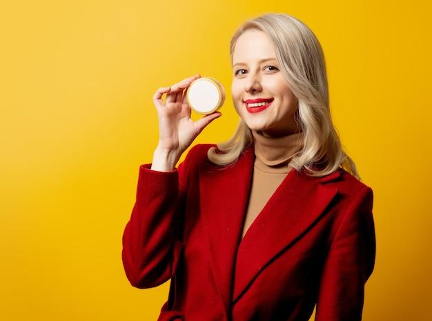 Mulher com casaco vermelho e frasco de creme na parede amarela