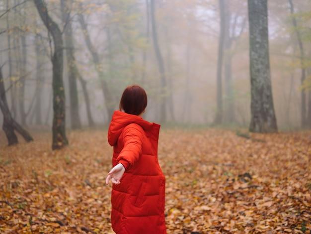 Mulher com casaco vermelho, folhas de outono, árvores, caminhada, neblina