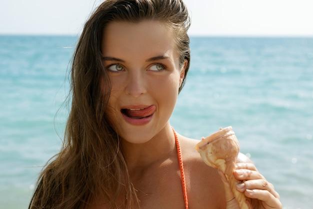 Mulher com casquinha de sorvete na praia
