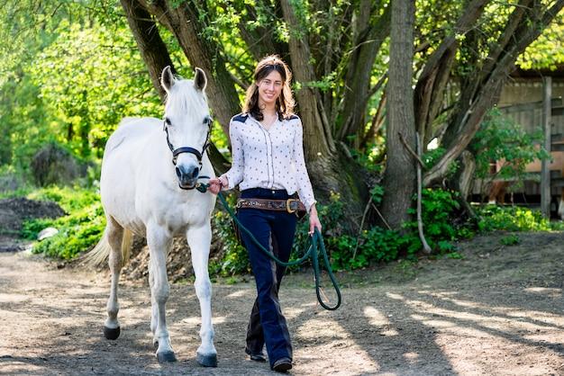 Mulher com cavalo branco andando