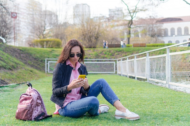 Mulher com celular ao ar livre na rua. mulher usando smartphone móvel.