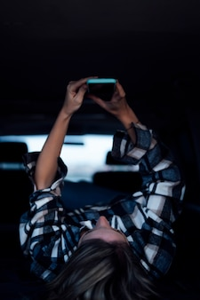 Mulher com celular dentro da van