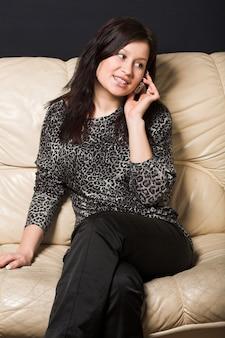 Mulher com celular sentado no sofá