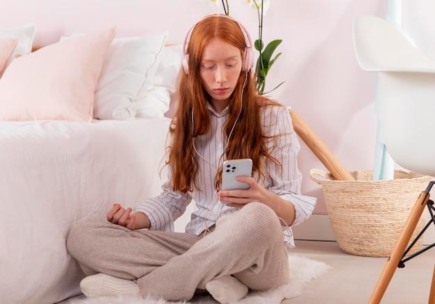 Mulher com celular trabalhando em casa