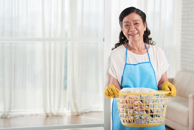 Mulher com cesto de roupa suja, sorrindo para a câmera