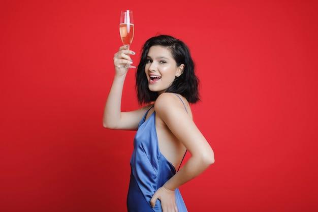 Mulher com champanhe olhando para a câmera sorrindo