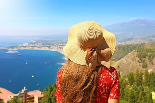 Mulher com chapéu apreciando a vista do vulcão etna da vila de taormina, na sicília, itália