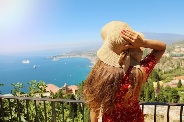 Mulher com chapéu, apreciando a vista do vulcão etna e do mar jônico de taormina, na sicília, itália