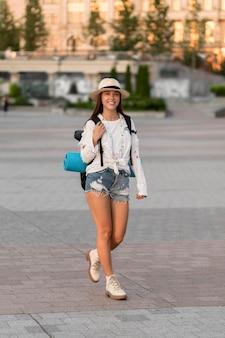 Mulher com chapéu carregando mochila enquanto viaja sozinha