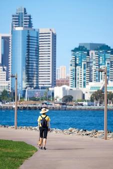 Mulher com chapéu clássico redondo passeando com o cachorro no parque à beira-mar em san diego