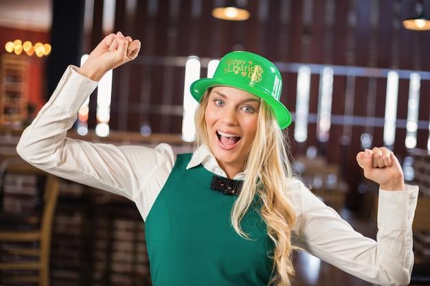 Mulher com chapéu de dia de st. patricks e braços para cima