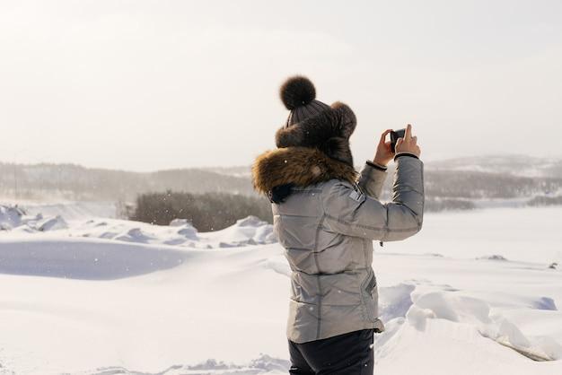 Mulher com chapéu de inverno fotografando um campo coberto de neve