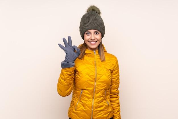 Mulher com chapéu de inverno sobre parede mostrando um sinal de ok com os dedos