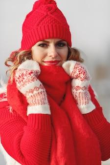 Mulher com chapéu de malha de inverno e lenço olhando para a câmera com um sorriso