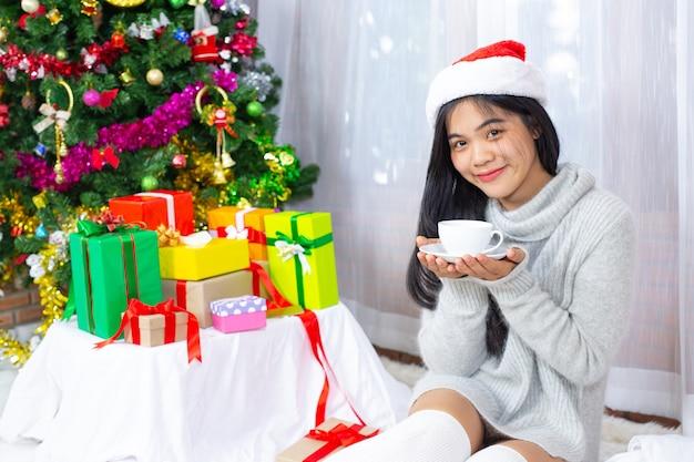 Mulher com chapéu de natal feliz com presente de natal