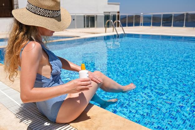 Mulher com chapéu de palha aplicando creme de proteção solar perto da piscina