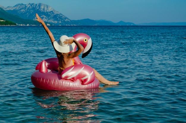 Mulher com chapéu de palha branco no flamingo floatie.