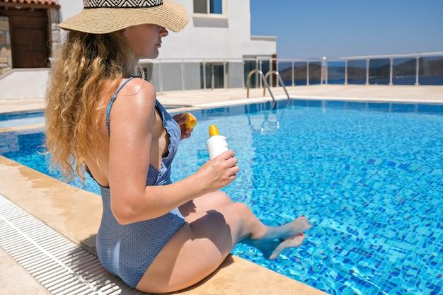 Mulher com chapéu de palha segurando protetor solar com protetor solar perto da piscina