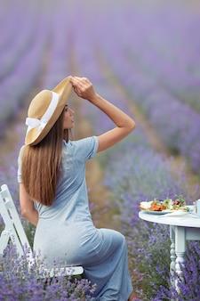 Mulher com chapéu de palha sentada à mesa no campo de lavanda