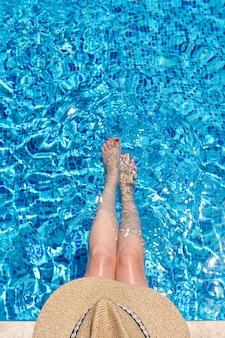 Mulher com chapéu de palha sentada na piscina com as pernas na água