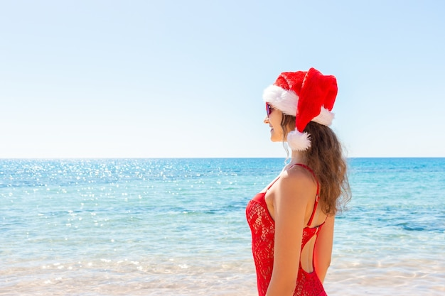 Mulher com chapéu de papai noel à beira-mar