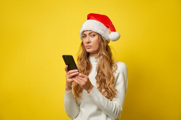 Mulher com chapéu de papai noel amarelo com smartphone na mão