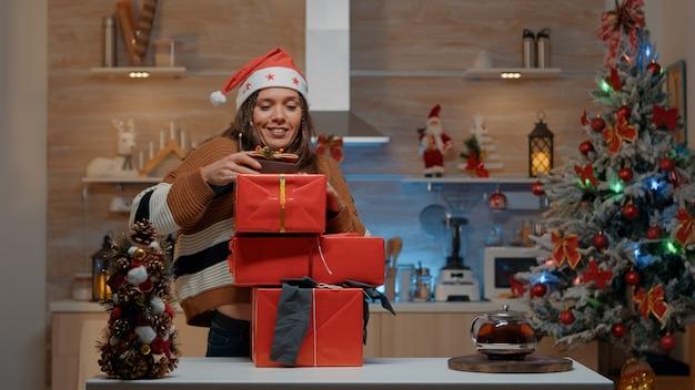 Mulher com chapéu de papai noel carregando presentes em cozinha decorada