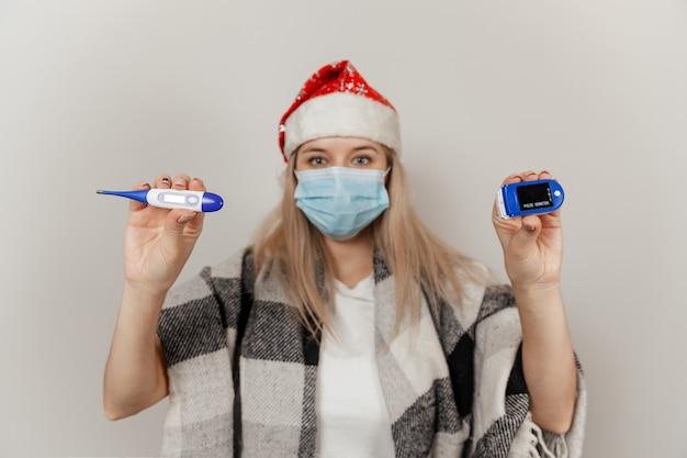 Mulher com chapéu de papai noel e máscara médica protetora segurando termômetro e oxímetro de pulso