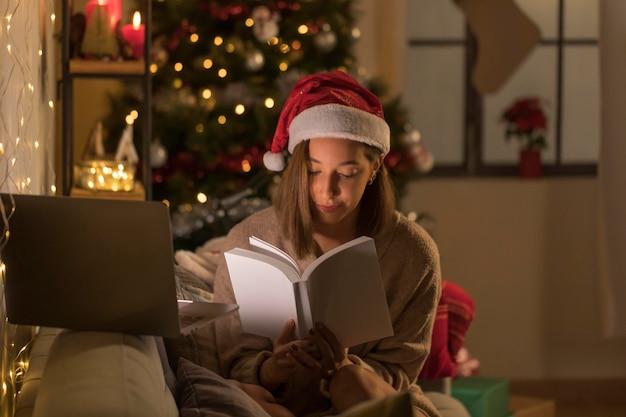 Mulher com chapéu de papai noel lendo livro na frente do laptop
