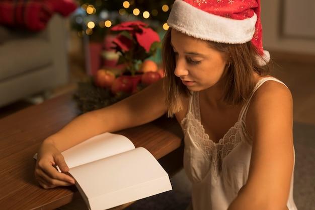 Mulher com chapéu de papai noel lendo um livro sobre o natal
